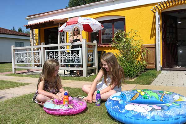 Children sitting on grass outside Wavesurfer Bungalows at Welcome Family Holiday Park