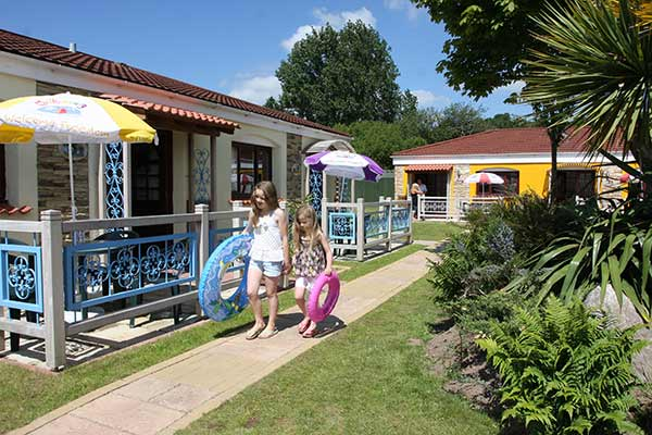Girls walking along outside aq Wavesurfer Bungalows at Welcome Family Holiday Park