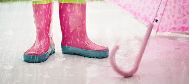 Child Wearing Wellie boots and umbrella on a Rainy Day