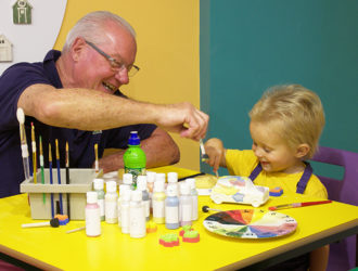 Child painting with his Grandad at the Painthub