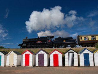 Dartmouth Steam Railway, train travelling above beach huts in Paignton, Devon.