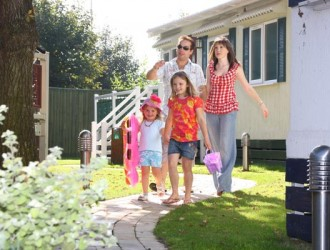 Family outside a lodge at Welcome Family Holiday Park