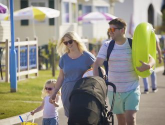 Family with baby and toddler walking in Welcome Family Holiday Park