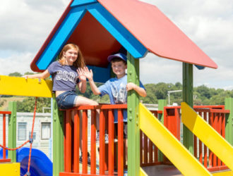 Two children waving from the fun park at Welcome Family Holiday Park