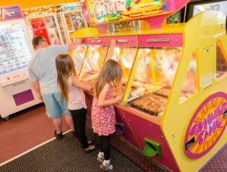 Kids playing on the coin drop machine at the arcade in Welcome Family Holiday Park