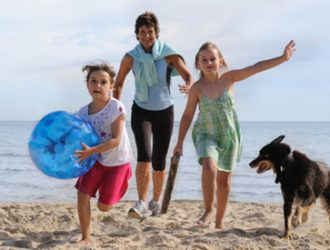 Children playing on the beach with a dog.