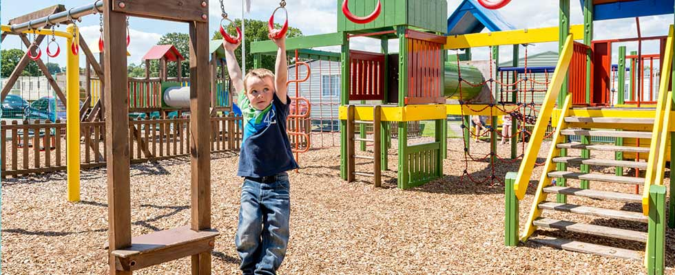 Boy swinging in fun park at Welcome Family Holiday Park