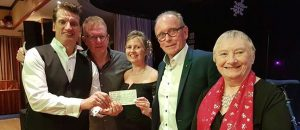 Mark Price giving a cheque for Cancer Research UK to The Sunflower Bunch, Dawlish.