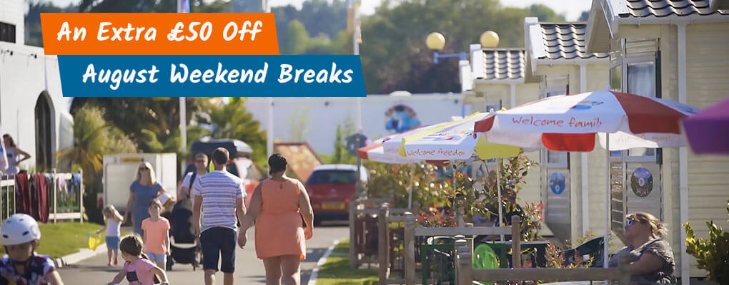 £50 Off August Weekend offer showing image of families and caravans at Welcome Family Holiday Park