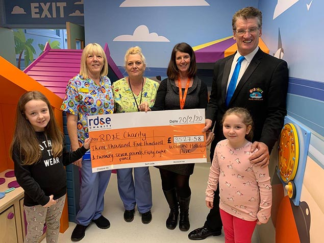 entertainment team handing over charity cheque